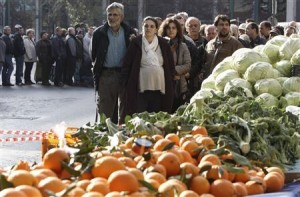 People line up for fruits and vegetables freely distributed by farmers during a protest against high production costs outside the Agriculture Ministry in Athens