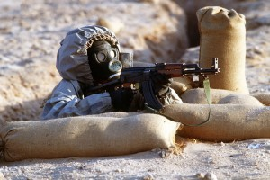 Syrian soldier wearing chemical warfare mask aims AK47