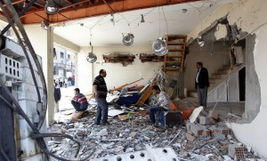 The owner of a shop and his family members wait in his damaged shop at the site of a twin bomb blast in the town of Reyhanli in Hatay province, near the Turkish-Syrian border