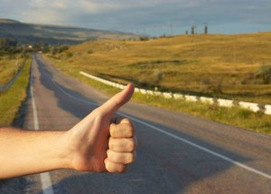 Hand of hiker man at rural mountain road. Daybreak.