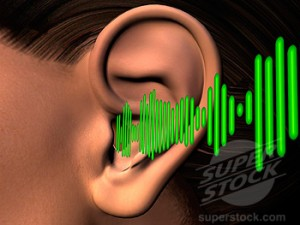 Close-up of a human ear listening to sound waves