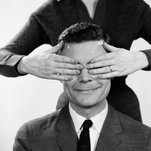 h-armstrong-roberts-woman-using-hands-to-cover-eyes-of-smiling-man