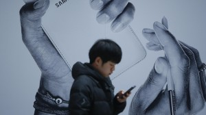 A passenger using his mobile phone walks past an advertisement promoting Samsung Electronics' Galaxy Note 3 at its exhibition hall at a railway station in Seoul