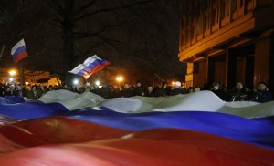 People carry a giant Russian flag during a pro-Russian rally in Simferopol, Crimea
