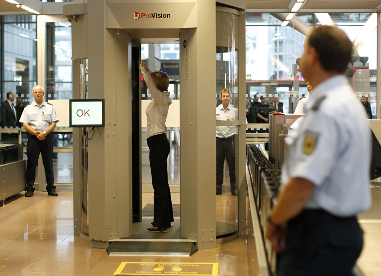 Security official demonstrates full body scanner during  photocall at Hamburg Airport