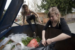 May Wollf, 28, climbs into a dumpster while Robin Pickell tears open a garbage bag in an alley behind Commercial Drive in Vancouver, British Columbia April 10, 2012.
