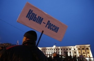 "A man holds a poster reading, ""Crimea - Russia"" during a pro-Russian rally in Simferopol, Crimea"