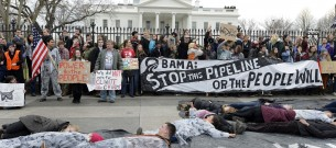 Environmentalists pretend to be dead on a black sheet symbolizing an oil spill as they rally in front of the White House and call on President Barack Obama to reject the Keystone XL oil pipeline, in Washington