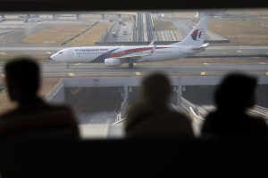 Passengers watch a Malaysia Airlines plane on a tarmac of the Kuala Lumpur International Airport