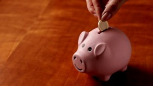 stock-footage-woman-drops-euro-coins-into-pink-piggy-bank-plenty-of-space-on-lhs-for-other-elements-to-be-added