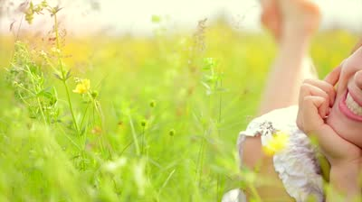 stock-footage-beauty-smiling-girl-lying-on-the-spring-meadow-with-wild-flowers-laughing-and-happy-enjoy-nature