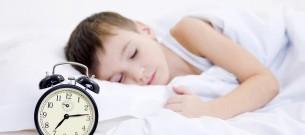 Little boy sleeping with alarm clock
