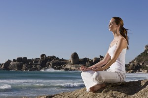 Young lady meditating on rock by sea